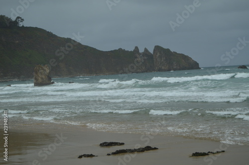 фотография  Shot Of The Waves Coming To The Beach And Away A Beautiful Cliff On The Beach Of El Aguilar On A Rainy Day