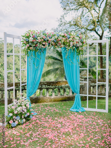 Fotografía  Wedding Arch with flowers, petals and blue cloth