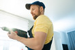 Serious busy muscular young bearded handyman in cap using power drill while making hole in wall