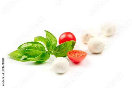 Deurstickers Buffel A closeup of Mozzarella cheese balls with fresh basil leaves and cherry tomatoes, the ingredients of the Italian Caprese salad, on a white background with copy space