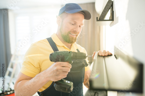 Obraz Cheerful optimistic handsome young bearded handyman in blue cap using cordless drill while screwing screw, he hanging shelf in apartment - fototapety do salonu