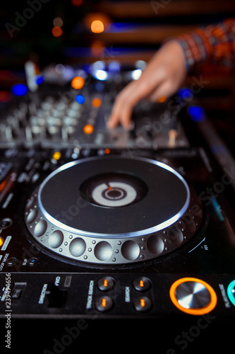 Dj mixes the track in the nightclub at party  In the