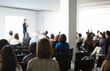 Presenter Presenting Presentation to Conference Audience. De-focused Blurred . Lecturer on Stage at Tech Forum. Speaker Giving Speech in Conference Hall Auditorium. Copy Space Screen Background.