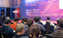 """""""Audience Watching A Presentation. Business. Female Presenter On Stage Giving Talk To Crowd Of People. Woman Speaker At  Investor Pitch Conference.  Defocused Blurred Presenter During Conference."""""""