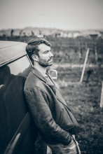 Young Man Casually Leans Against Vintage Car (T2 Bus Built In 1970), Black And White Image, Background Vineyards / Landscape