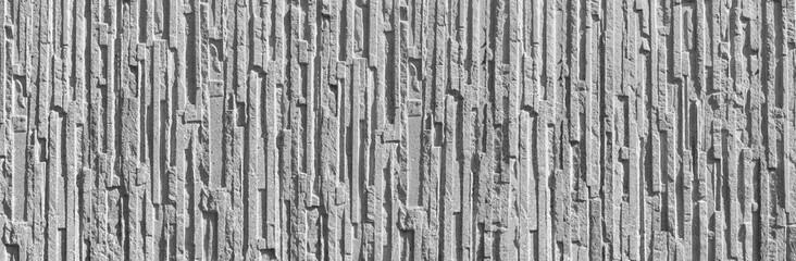 Panorama einer groben grauen Wand mit einem Relief aus Sichtbeton im Sonnenlicht