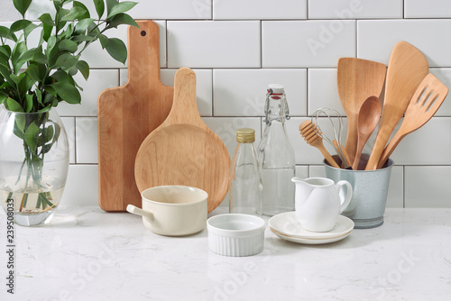 Cuadros en Lienzo  Simple rustic kitchenware against white wooden wall: rough ceramic pot with wooden cooking utensil set, stacks of ceramic bowls, jug and wooden trays