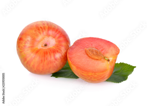 whole and half cut ripe fresh pluot on white background