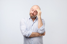 Portrait Of Tired And Annoyed Handsome European Man Iwith Beard, Leaning Head On Fist And Breathing Out From Boredom, Standing Unhappy Over Gray Wall
