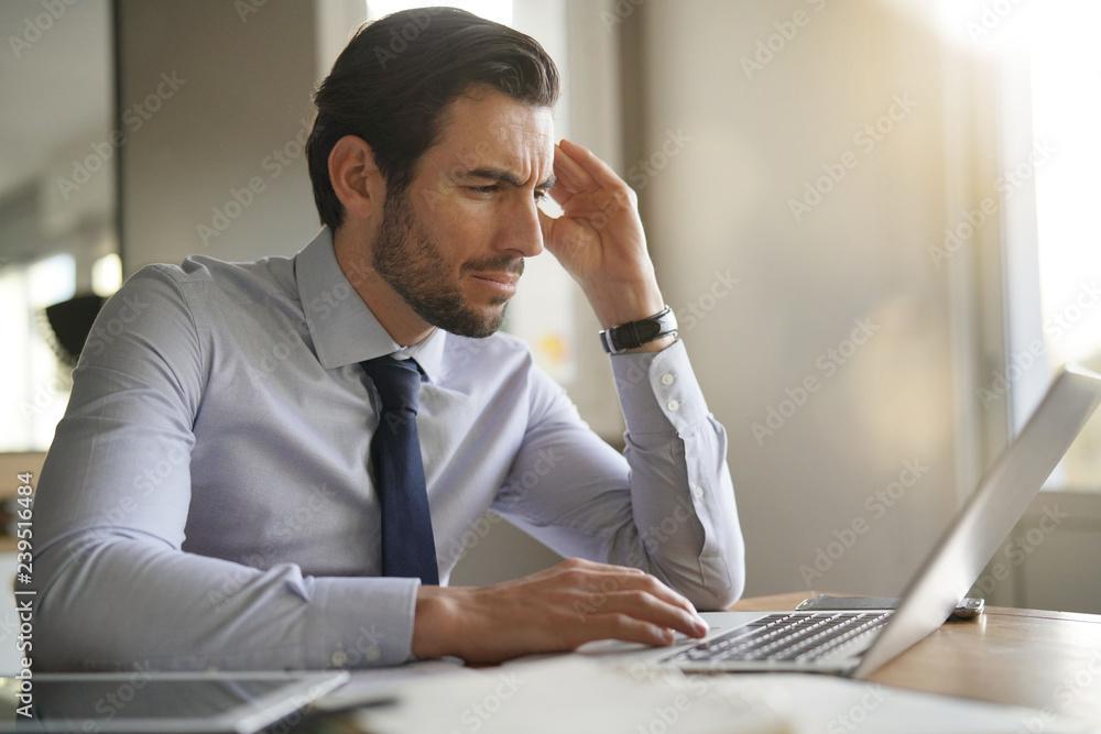 Fototapeta Handsome businessman concentrating on laptop in modern office