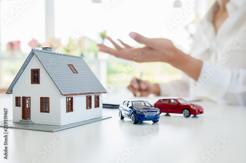 Fototapeta Car and House model with agent and customer discussing for contract to buy, get insurance or loan real estate or property background. obraz