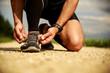 Wysportowany mężczyzna wiąże buty. Biegacz. Sport. Zdrowy styl życia