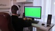 Man using PC computer with green screen chroma key at home
