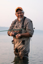 Caucasian Senior Male Tying A Fly On His Fly Fishing Line While Fishing For Salmon And Searun Cutthroat Trout In Puget Soud Near Port Orchard, Washington USA.