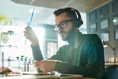 Portrait of handsome male designer holding color swatches in sunlight while thinking over creative project in office, copy space - 239529684