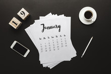 Top View Of Calendar, Wooden Cubes With 19 Numbers, Pencil, Cup Of Coffee And Smartphone On Black