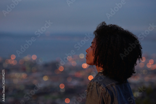 Woman looking at city lights from viewpoint Wallpaper Mural