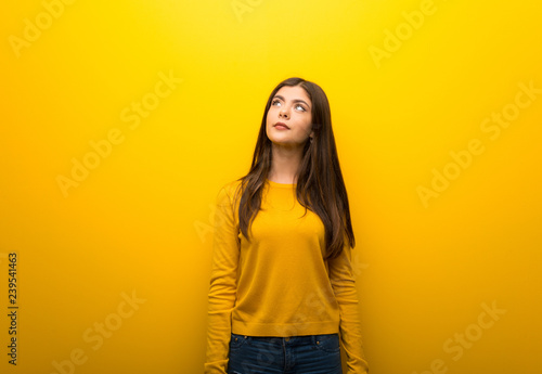 Pinturas sobre lienzo  Teenager girl on vibrant yellow background looking up with serious face