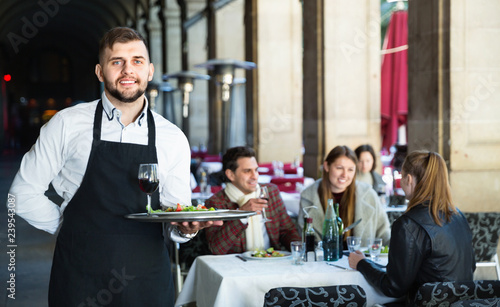 Fotografía  Portrait of smiling waiter with serving tray meeting restaurant guests