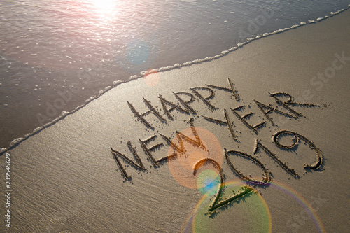 Zdjęcie XXL Szczęśliwa nowy rok 2019 wiadomość ręcznie pisany w gładkim piasku z wschodu słońca obiektywu racą nad nadjeżdżającą fala na plaży