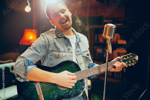 Talented bearded Caucasian musician playing acoustic guitar and singing at home studio. - 239547416