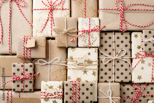 Christmas background with many decorative homemade gift boxes wrapped in brown kraft paper & red white twine. Flat lay.