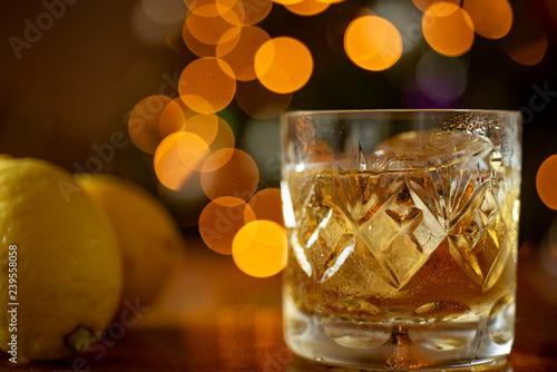 Glass of whiskey bourbon in a crystal glass up close shot Bokeh lights backgroun Wallpaper Mural