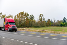 Big Rig Red Semi Truck Tractor Transporting Refrigerator Semi Trailer On The Straight Road On Trees And Field Background