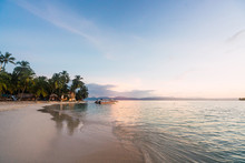 Sand Beach With Palms And Building Near Water Surface And Beautiful Sky