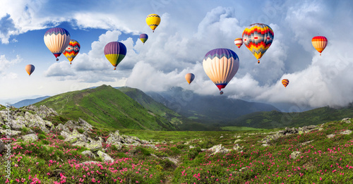 Multicolored hot air balloons on a mountain ridge covered with flowering rhododendrons