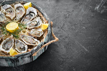 Fresh Oysters With Lemon In Wooden Box. On A Black Stone Background. Top View. Free Copy Space.