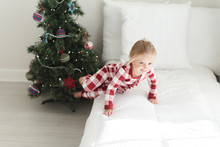 Young Girl Sitting On A Bed Next To A Christmas Tree