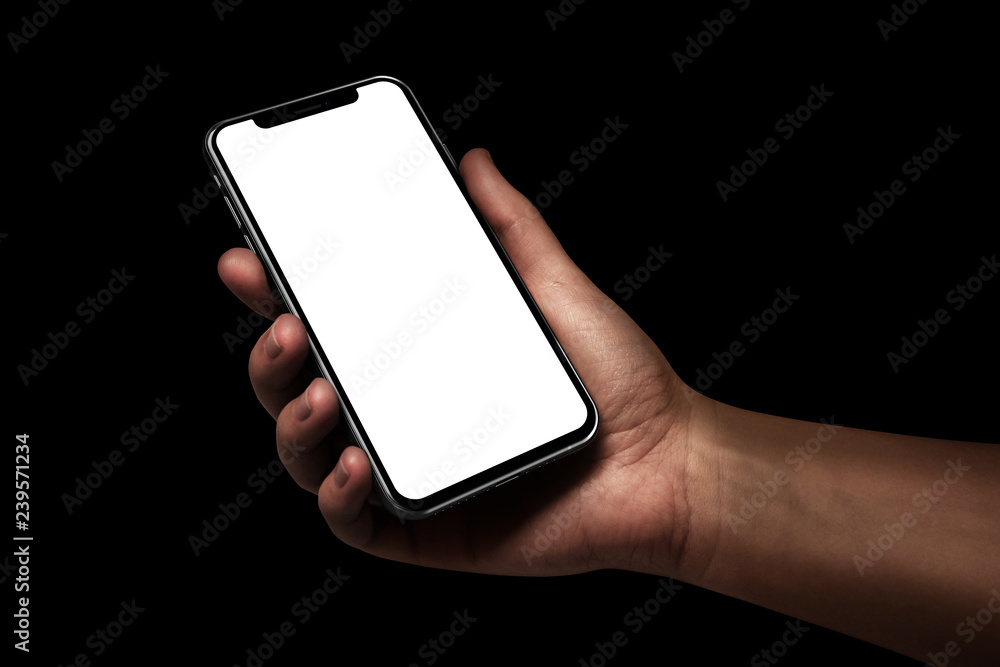 Fototapeta Woman hand holding the black smartphone with blank screen isolated on black