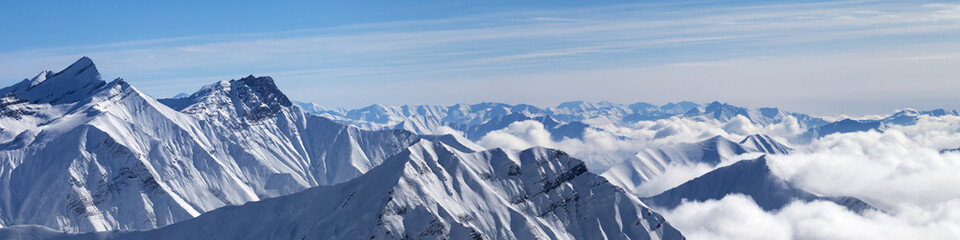 Panorama of snowy mountains in clouds