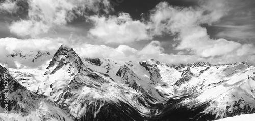 Foto auf Gartenposter Gebirge Black and white panorama of snowy winter mountain in sunlight clouds