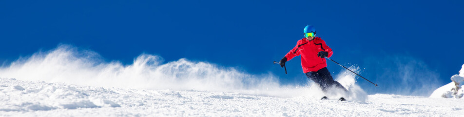 Man skiing on the prepared slope with fresh new powder snow