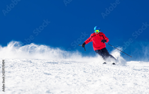 fototapeta na lodówkę Man skiing on the prepared slope with fresh new powder snow