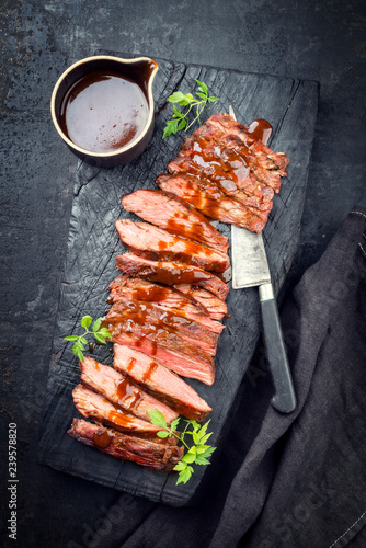 Traditional American barbecue dry aged flank steak sliced with hot sauce and chili as top view on an old carbonized board