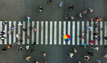 Aerial. Pedestrian Crossing Crosswalk. Top View. In The Center Is A Man With A Colorful Umbrella.