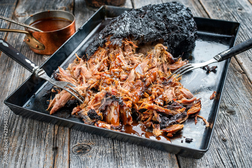 Traditional barbecue pulled pork piece of Bosten butt torn to bits with hot sauce in casserole as closeup on a board