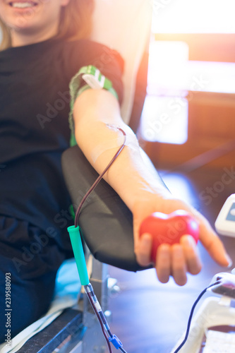 Fototapeta young woman as blood donor at donation with a bouncy ball holding in hand
