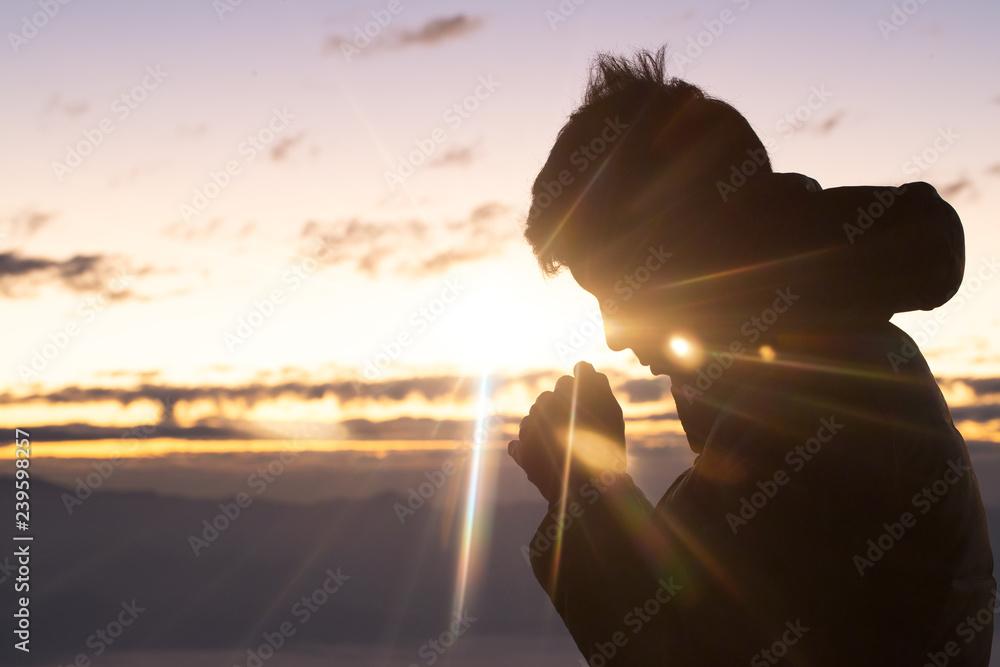 Fototapety, obrazy: Silhouette of christian man hand praying,spirituality and religion,man praying to god. Christianity concept.