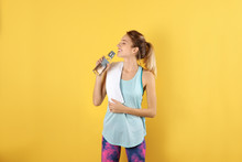 Beautiful Young Woman In Sportswear With Towel And Bottle Of Water On Color Background
