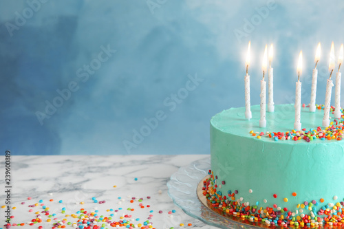 Fresh delicious birthday cake with candles on table against color background Canvas Print