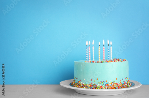 Fresh delicious birthday cake with candles on table against color background. Space for text