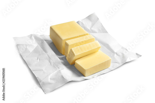 Photo  Cut block of fresh butter with wrapper on white background