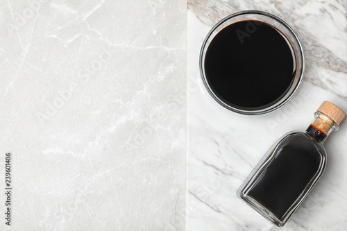 Bottle and bowl with balsamic vinegar on table, top view. Space for text