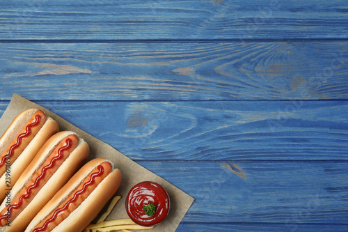 Composition with hot dogs, french fries and sauce on color wooden table, top view. Space for text