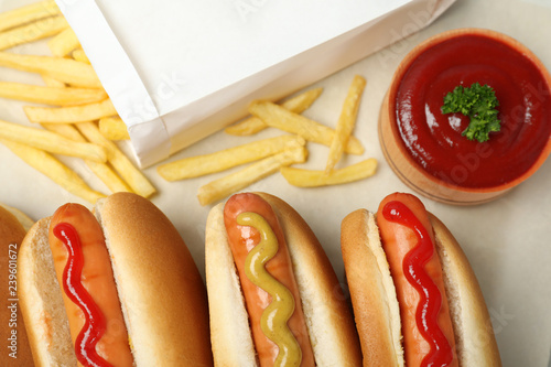 Composition with hot dogs, french fries and sauce on parchment paper, top view