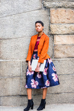 Young African American Woman Thinking Outside In New York, Wearing Orange Red Jacket, Flower Patterned Skirt, Black Boot Shoes, Holding Laptop Computer, Standing By Stone Wall, Narrowing Eyes, Puzzled